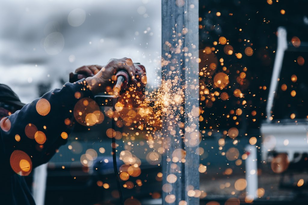 Artisan qui scie du métal avec étincelles