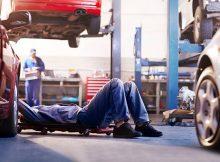 Garagiste qui répare une voiture dans un garage auto
