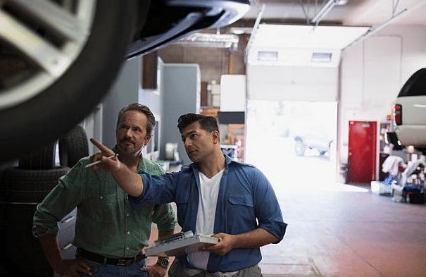 Garagiste qui examine une voiture et explique les réparations à un client