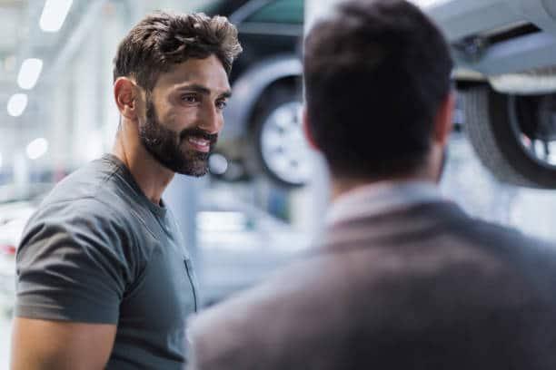 Garagiste qui conseille un client dans un garage auto
