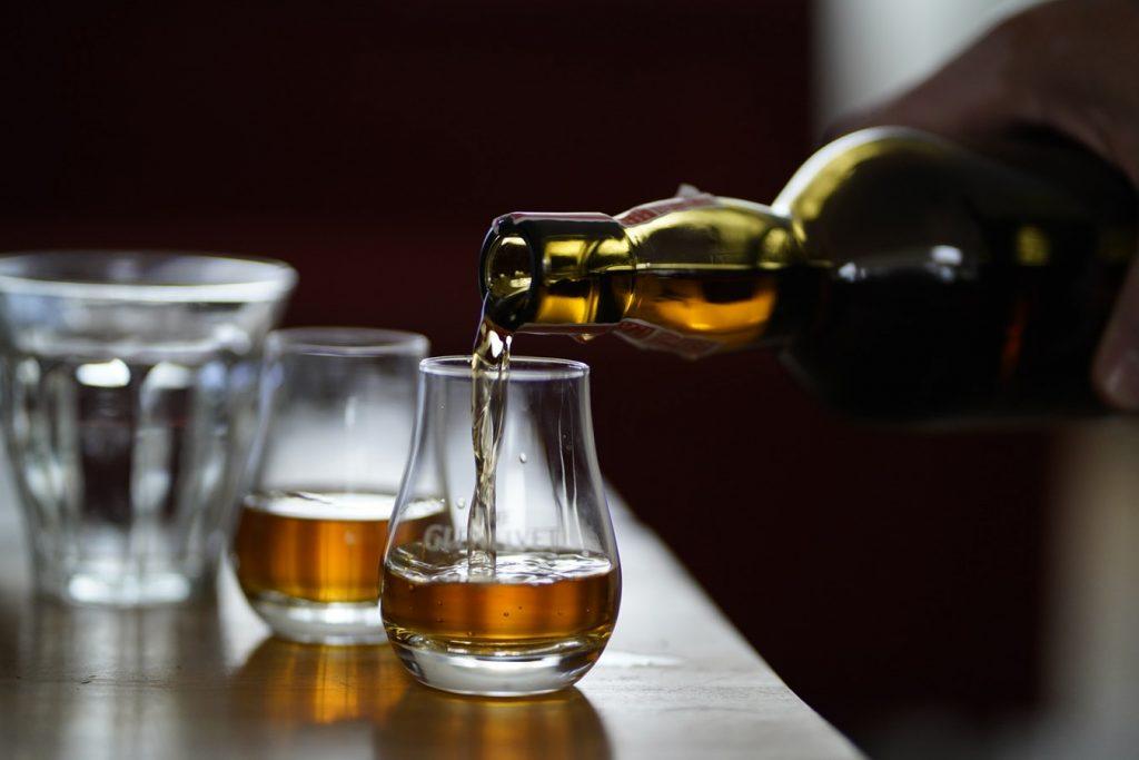 Jeune homme qui sert des verres de whisky issus d'une distillerie