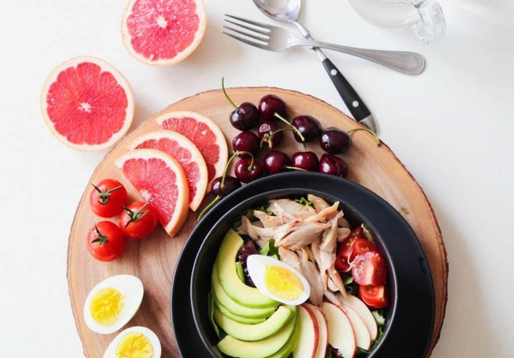 buddha bowl avec avocat pomme tomate poulet oeuf, autour pamplemousse cerises et tomates cerises