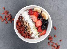 bol petit déjeuner sain avec fruits, noix de coco, baies de goji