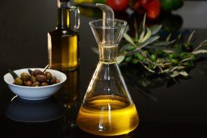 Deux bouteilles d'huile d'olive posée sur une table avec un bol rempli d'olives et une branche d'olivier