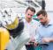 deux hommes regardant une tablette devant une machine industrielle