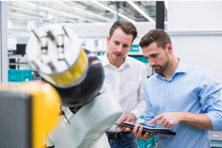 deux hommes regardant une tablette devant une machine industrielle